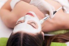 Seifen-, Tuch- und Blumenschneeglöckchen Übergeben Sie das Anwenden der Ernährungsmaske auf weiblichem Gesicht im Badekurort Stockfotos