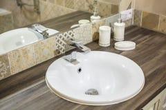 Seifen- und Shampoozufuhren auf Wasserhahnwanne mit Hahn im teuren Dachbodenbadezimmer stockfotografie