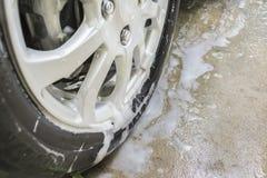 Seifenblasen auf Rad vor Waschanlage Stockfoto