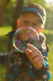 Seifenblasen, die auf einen grünen Rasen schwimmen Lizenzfreie Stockfotografie