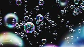 Seifenblasen gegen einen unbedeutenden schwarzen Hintergrund lizenzfreies stockfoto
