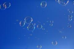 Seifenluftblasen, die in einen blauen Himmel schwimmen Stockfotos