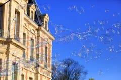 Seifenluftblasen, die in einen blauen Himmel schwimmen Lizenzfreie Stockfotografie