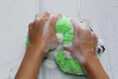 Seifige Hände mit grünem Schwamm Lizenzfreie Stockfotos
