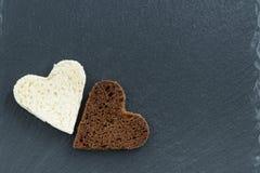 Seigle et pain blanc grillés sous forme de coeur sur l'obscurité Photographie stock libre de droits