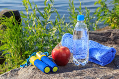 Seilspringen, Apfel, Tuch und Flasche mit Wasser auf Felsen mit Meer s Stockbilder
