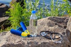 Seilspringen, Stethoskop und Flasche mit Wasser auf Felsen mit dem Meer SH Lizenzfreies Stockfoto