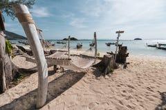 Seilwiegenschwingen, das am Holz auf dem Strand mit hölzernem Boot im tropischen Meer hängt lizenzfreies stockbild