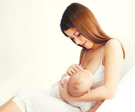 Sein de alimentation de jeune mère son bébé à la maison image stock