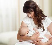 Sein de alimentation de jeune mère son bébé à la maison dans la chambre blanche photo stock