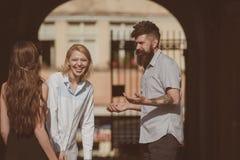 Sein so lustiges Freundschaft fängt mit Lächeln an Bärtiger Mann und hübsche Frauen, die auf Straße lächeln Freunddatierungsfreun stockfoto