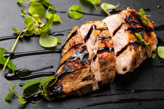 Sein rôti de poulet d'un plat en pierre noir avec du vinaigre balsamique et l'origan photos libres de droits