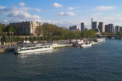 Seine bank with berth and ship. The bank of Seine river in Paris. New cruise ships along with old steam-boats. Historical and modern buildings are on the Stock Photo