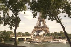 Paris, the Seine, and the Eiffel tower - France. The Seine in Paris with its boats, and its bridges. In backs plan there is the tower Eiffel. In front of the royalty free stock images