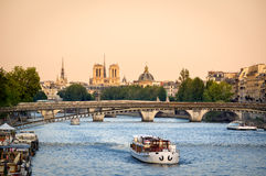 Seine River Bridges and Notre Dame Cathedral, Paris, France. View of the Seine River in Paris with Passerelle de Solferino bridge and passing tour boat. In the Royalty Free Stock Photo