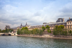 Seine river coast with Louvre museum facade. PARIS, FRANCE - AUGUST 07, 2014: Seine river with Louvre museum facade on other side Stock Photo