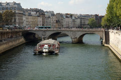 Seine River Cruise Ship. Photo of cruise ship on the seine river in paris france on 9/15/14.  These boats offer hop on hop off convenience at various stops Royalty Free Stock Photography