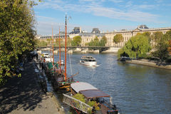 Seine river docks and boats with Louvre Museum in background Stock Image