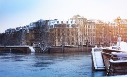 Seine river embankment in snow, Paris, France. Seine river embankment with trees and buildings in snow, Paris, France stock photography