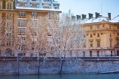 Seine river embankment after snowfall in Paris. Beautiful view of Seine river embankment with snow-covered trees and buildings after snowfall in Paris, France stock photo