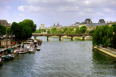 Seine riverbank with Paris landmarks, France. Boats moored along banks of the River Seine with views of landmarks Pont des Arts and Louvre Museum on sunny day in Stock Images