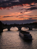 Seine Sunset, Paris. Late spring sunset on the Seine in Paris with a boat about to pass the Pont Royal bridge. Focus on boat Royalty Free Stock Photos