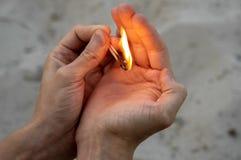 In seinen Händen brennende matchs und Sandhintergrund stockbild