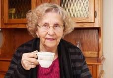 Seinorvrouw met kop thee Stock Foto's