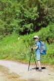 Seis años del muchacho caminan en el camino de tierra Foto de archivo libre de regalías