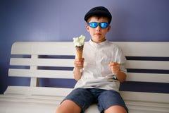 Seis años lindos de muchacho que come el helado Imagen de archivo libre de regalías