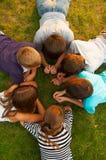 Seis adolescentes y muchachas que mienten en la hierba Fotografía de archivo