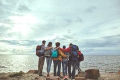 Seis amigos que abrazan en la orilla de mar imágenes de archivo libres de regalías