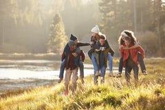 Seis amigos se divierten que llevan a cuestas en el campo por el lago Imagen de archivo