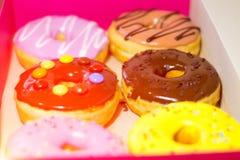 Seis anéis de espuma coloridos em uma caixa cor-de-rosa Anéis de espuma doces com esmalte Fotografia de Stock