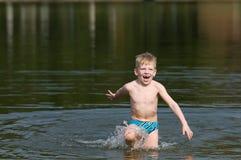 Seis anos de menino idoso que sai o lago Imagens de Stock Royalty Free