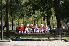 Seis bebês que sentam-se no parque natural verde urbano no banco fotos de stock