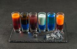 Seis bebidas coloridas diferentes do tiro, alinhadas em um pla preto da pedra Fotografia de Stock Royalty Free