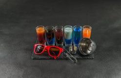 Seis bebidas coloridas diferentes do tiro, alinhadas em um pla preto da pedra Imagem de Stock