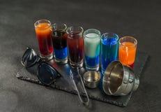 Seis bebidas coloridas diferentes do tiro, alinhadas em um pla preto da pedra Fotografia de Stock
