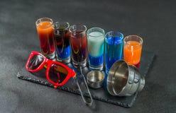 Seis bebidas coloridas diferentes do tiro, alinhadas em um pla preto da pedra Imagens de Stock Royalty Free