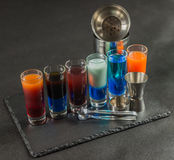 Seis bebidas coloridas diferentes do tiro, alinhadas em um pla preto da pedra Fotos de Stock Royalty Free