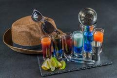 Seis bebidas coloridas diferentes do tiro, alinhadas em um pla preto da pedra Foto de Stock Royalty Free