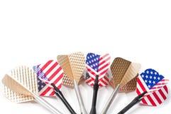 Seis blancos que juegan los dardos, pizca los E.E.U.U. señalan colores y la pluma por medio de una bandera de oro,   Imagen de archivo libre de regalías