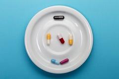 Seis cápsulas coloridas em uma placa imagem de stock