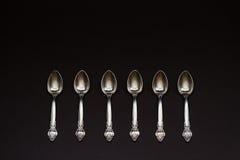 Seis colheres de prata em seguido no fundo preto imagens de stock
