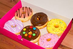 Seis coloriram anéis de espuma em uma caixa cor-de-rosa em um fundo de madeira D doce Imagem de Stock