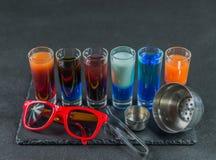 Seis diversas bebidas coloreadas del tiro, alineadas en un pla negro de la piedra Imagen de archivo libre de regalías