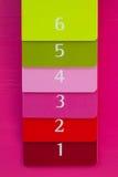 Seis diversos diarios del color en un escritorio de madera rosado Imágenes de archivo libres de regalías