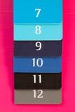 Seis diversos diarios del color en un escritorio de madera rosado Imagen de archivo