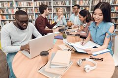 Seis estudantes étnicos, raça misturada, indiano, asiático, afro-americano e branco cercados com os livros na biblioteca fotos de stock